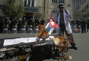A medical student burns a Cuba flag during a protest by members of Bolivia's health system in La Paz