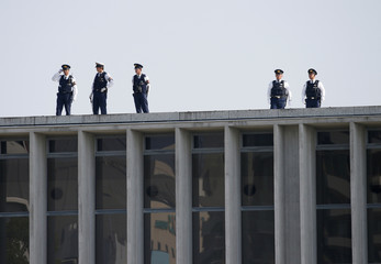 Police officers stand guard atop of a building before Obama's arrival at Hiroshima Peace Memorial Park and Museum