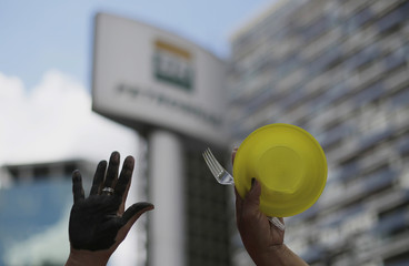 Member of Brazil's Movimento dos Sem-Teto, Roofless Movement, holds an empty plate during protest in front of the Petrobras headquarters in Sao Paulo