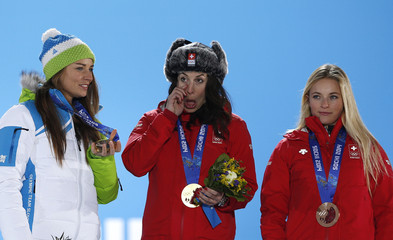 Joint gold medalists Switzerland's Gisin and Slovenia's Maze react next to bronze medalist Switzerland's Gut during the medal ceremony for the women's alpine skiing downhill race at the Sochi 2014 Winter Olympic Games in Sochi