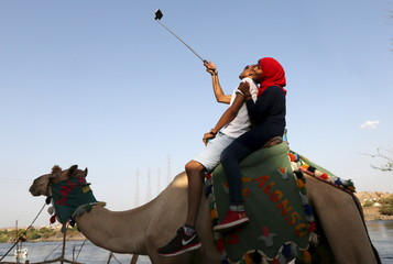A couple takes a selfie while riding on a camel in Gharb Suheil village