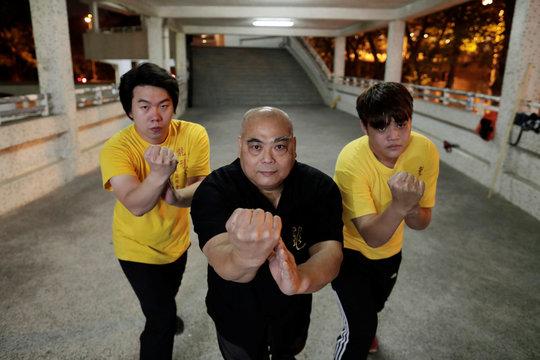 Dragon Sign Kung Fu master Wong Yiu-kau poses with his students at a martial arts class in Hong Kong