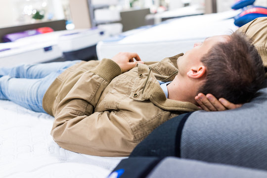 Young man trying out laying down on mattress on display in store