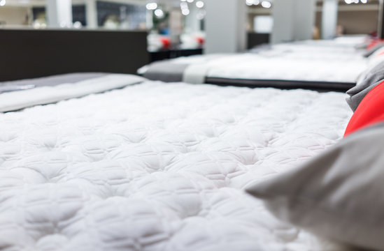 Closeup of many mattresses on display in store