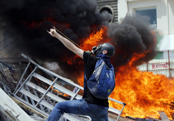 A protester uses a slingshot to throw stones at riot police during a protest at Taksim Square in Istanbul