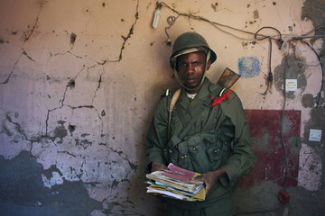 Malian soldier holds papers next to a wall pockmarked with bullet holes