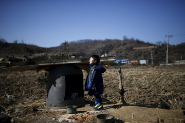 A boy stands in the sunlight at a border village just south of the demilitarized zone where loudspeakers are installed, in Yeoncheon