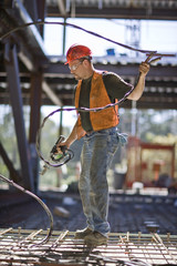 Male construction worker working with a power tool on a construction site.