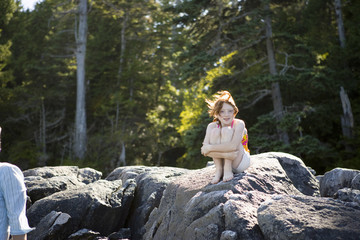 Portrait of a young girl sitting on rocks holding her legs.