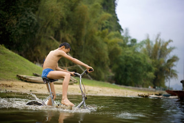 Boy riding bicycle in water