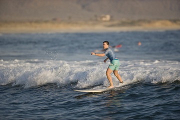 Young woman surfing on a small wave