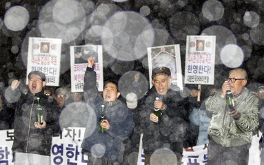 Anti-North Korea protesters shout slogans as they pop champagne during a rally celebrating North Korea's leader Kim Jong-il's death as snow falls in Seoul