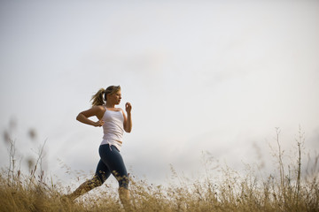Teenage girl running along a track in a field.
