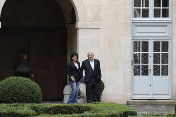 Former IMF chief Strauss-Kahn and wife walk in the courtyard of their residence in Paris