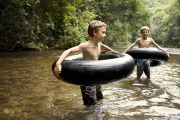 Two young boys knee deep in water hold their inflatable rings during an outdoors adventure.