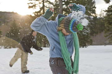 Young woman being hit from behind by a snow ball while standing in a snowy field.
