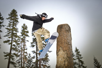 Young man jumping next to a large tree trunk on his snowboard.