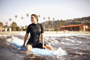 Young female surfer sitting on surfboard,  waiting for a wave.