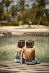 Two happy young children relaxing on a wooden pier on their tropical island holiday.