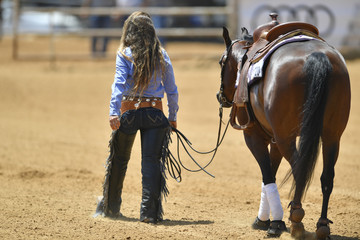 The rear view of a rider in cowboy chaps and boots leads the horse out from the sand field