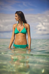 Pretty young woman wading in the sparkling tropical ocean.