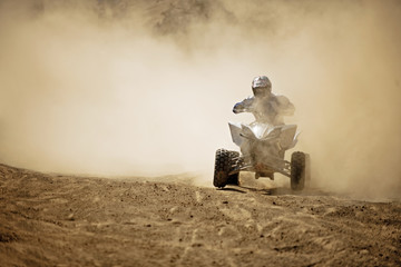 Quadbiker rides through dusty dirt road.