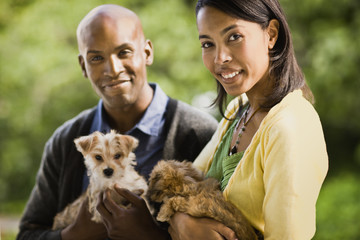 Young heterosexual couple smile as they hold puppies and pose for a portrait.