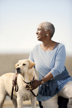 Portrait of a smiling mature woman kneeling next to her dog.