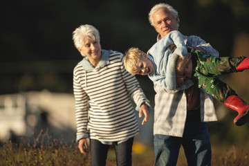 Small boy laughs as his grandfather playfully hefts him up horizontally and his grandmother smiles as she watches while they walk together outside.