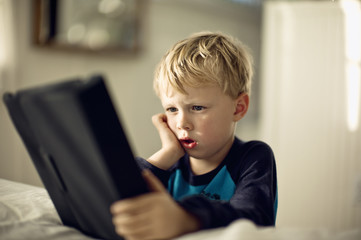Young boy looking serious as he plays with a portable information device.