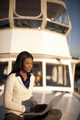 Woman using her laptop on a boat.