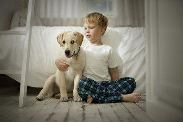 Young boy sitting on floor with dog.