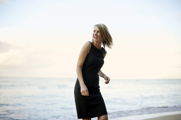 Happy businesswoman walking on the beach.