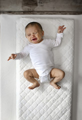 Crying baby lying on changing table.