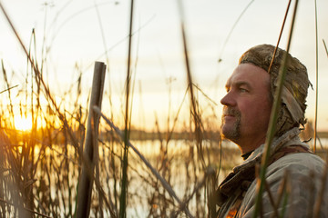 Mid-adult man hiding in reeds near a lake while duck hunting.