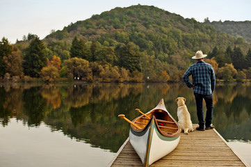 Canoeist standing on the edge of a lake pier with his dog.