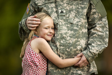 Young girl hugging her father's waist.