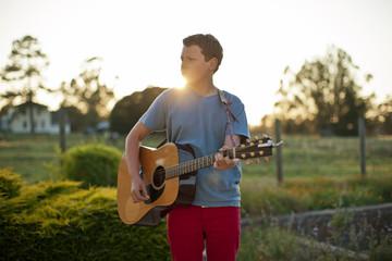 Teenage boy playing an acoustic guitar.