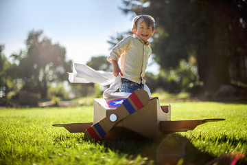 Young boy plays with his cardboard box plane in the garden.