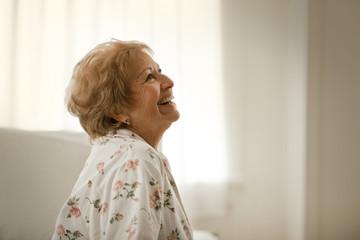 Laughing senior woman wearing floral pajamas.
