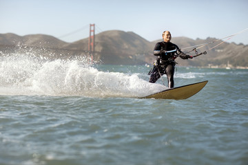 Mid adult man kite surfing near the Golden Gate Bridge, San Francisco, USA.