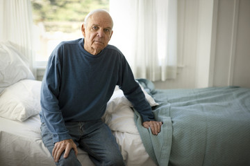 Portrait of a concerned senior man sitting on a bed in his bedroom.