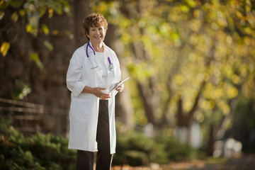 Portrait of a confident female doctor standing in a park.