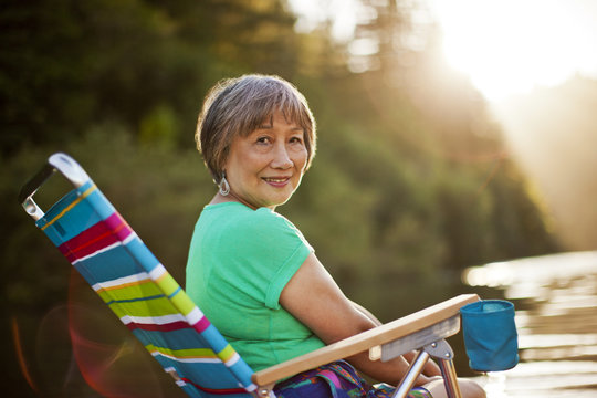 Portrait of a happy senior woman sitting in a deck chair at a lake.