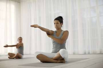 Young woman and young girl stretching their arms while doing yoga.