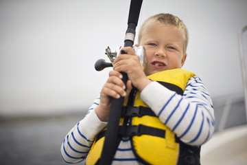 Portrait of a young boy struggling with a fishing rod.