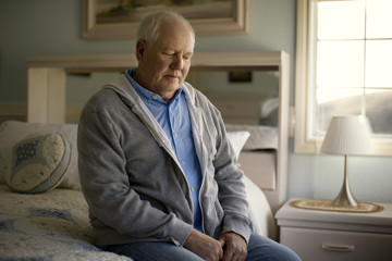 Depressed mature man sits sadly on his bed.