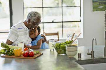 Happy young boy hugging his grandfather while they prepare a salad.