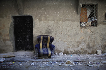 A chair sits outside an empty house at the front line in Aleppo