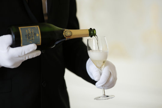 An employee serves a glass of Champagne during the traditional wine harvest at the Champagne house Deutz in Ay